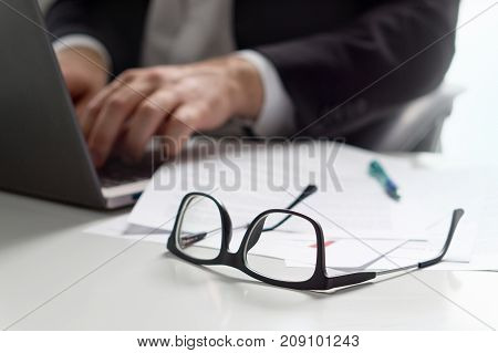 Business man writing with laptop in office with glasses on table.