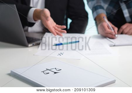 Team in law firm working in office. Lawyers discussing and writing. Business people having legal meeting. Pile of paper on table with scale and justice symbol.