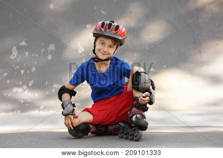 Cute boy on rollers sitting in skate park