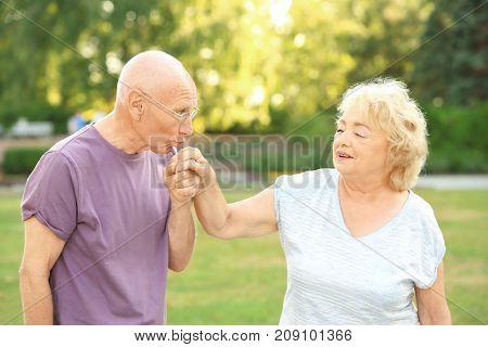 Elderly man kissing hand of senior lady in park