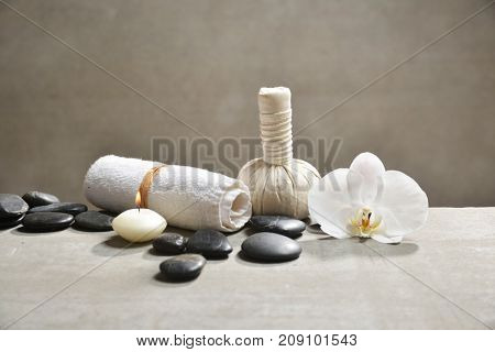 White orchid with pile of black stones and white candle, o herbal ball , on gray background