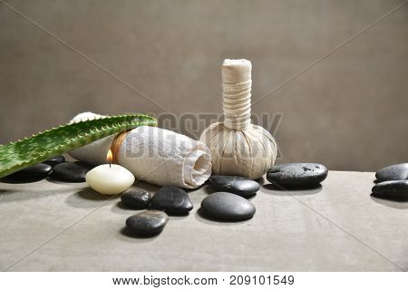 Aloe with pile of black stones and white candle, herbal ball ,towel on gray background