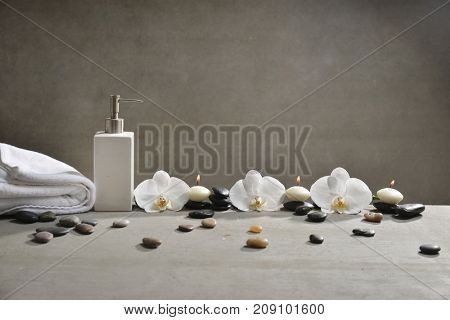 Three white orchid with pile of gray stones ,towel, bottle, oil ,candle on gray background