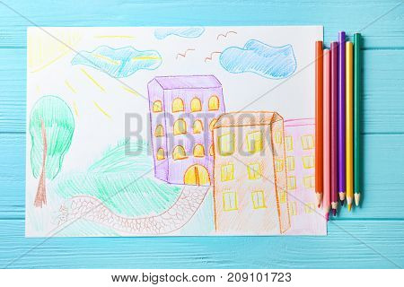 Child's drawing of buildings in city on blue background