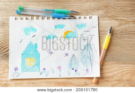 Child's drawing of house and trees on wooden background