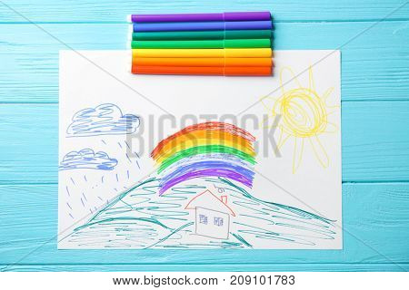 Child's drawing of house and rainbow on blue background