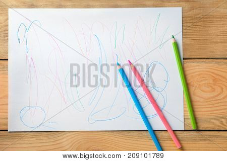 Colorful abstract child's drawing on wooden background