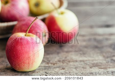 Stack of fuji apple and in basket put on wood table for background or wallpaper in vintage tone style. Delicious sweet and juicy fuji apple for salad cooking or bakery.Fuji apple has origins in Japan. Fresh apple concept for your design.