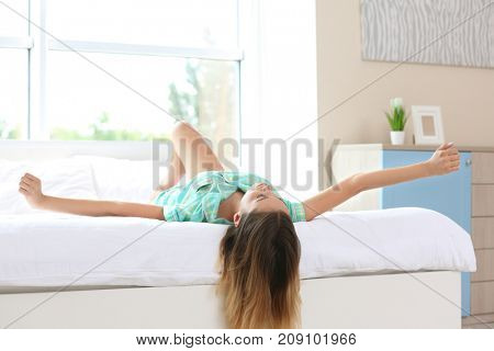 Young woman lying on bed in morning