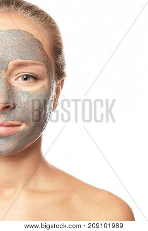 Young woman with facial mask on white background