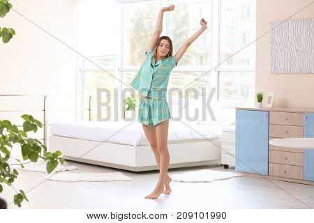 Young woman stretching at home in morning