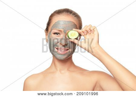 Young woman with facial mask and cucumber slice on white background