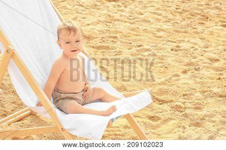 Little boy sitting on beach chair at seacoast