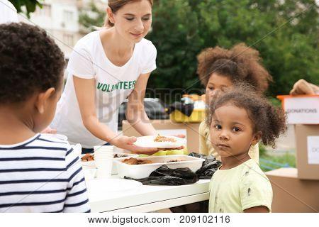 Volunteer sharing food with poor African children outdoors