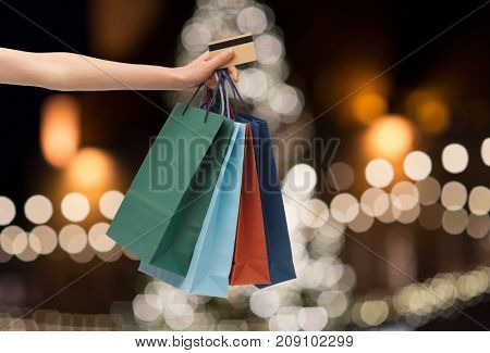 sale, holidays, consumerism and people concept - close up of hand holding shopping bags and credit card over christmas tree lights background