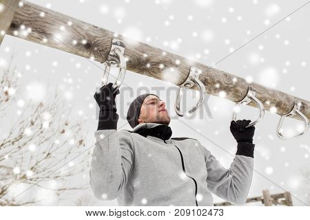 fitness, sport, exercising, training and people concept - young man doing pull ups on horizontal bar outdoors in winter