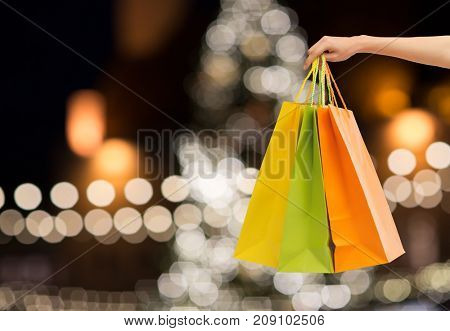 sale, holidays, consumerism and people concept - close up of hand holding shopping bags over christmas tree lights background