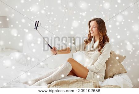 technology, christmas, winter and people concept - happy young woman in bed taking picture by smartphone selfie stick at home bedroom with snow