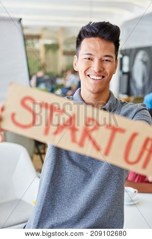Asian man holds sign in start-up at conference room