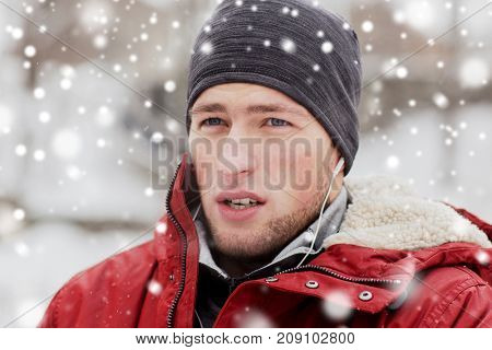 people, christmas, winter and season concept - close up of man in jacket and hat with earphones listening to music outdoors