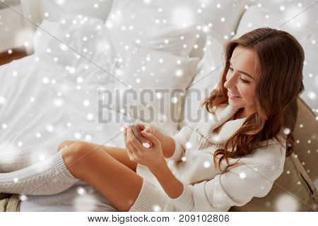 technology, communication and people concept - happy young woman in bed and texting on smartphone at home bedroom with snow