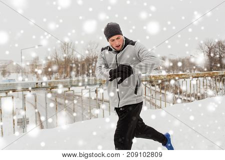 fitness, sport, people, technology and healthy lifestyle concept - young man in earphones running along snow covered winter bridge and looking at activity tracker or smart watch