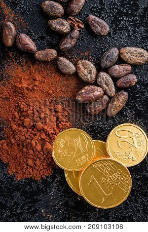 Dark cocoa powder, cocoa beans and chocolate euro coins. Top view.