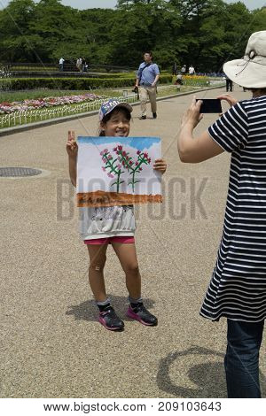 Kyoto, Japan - May 21, 2017: Child is showing a painting made by herself in the Kyoto botanical garden to learn the shape of flowers and plants