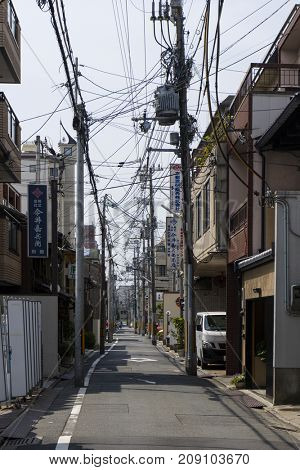 Kyoto, Japan - May 21, 2017: Japanese electricity pylon and cables overground in an alley in Kyoto