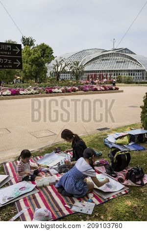Kyoto, Japan - May 21, 2017: Children are painting in the Kyoto botanical garden to learn the shape of flowers and plants