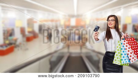 A woman is a buyer with a credit card with gift packages on the background of a market, a shopping center.