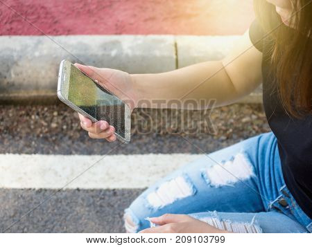 Woman picking up and holding cracked screen smart phone from the ground