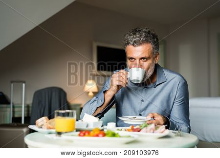Mature, handsome businessman having breakfast in a hotel room, drinking cofee.