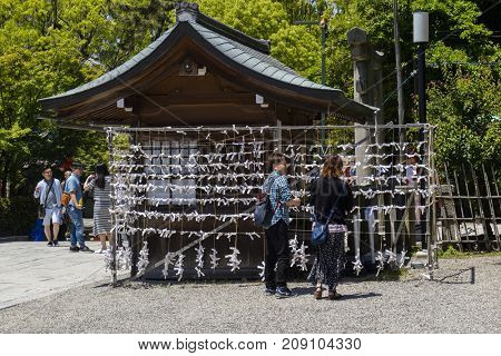 Kyoto, Japan - May 19, 2017: O-mikuji fortune papers tied to a rack at  at the Yasaka jinja shrine in Kyoto