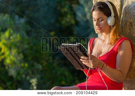 casual woman working with a tablet pc, with headphones, outdoor