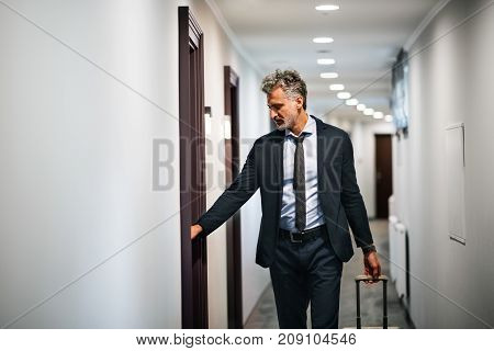 Mature businessman with luggage in a hotel corridor, opening the door of the room. Handsome man pulling suitcase.
