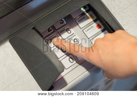 Woman entering her pin code number to atm machine. Money and cash withdrawal concept. Hand on buttons and keypad.