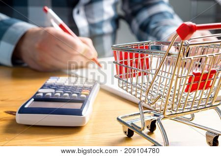 Rising food and grocery store prices and expensive daily consumer goods concept. Man counting food money with pen, paper and calculator at home. Budget of disadvantaged and low income family.