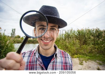 A cheerful young man with a funny face in a hat holds a magnifying glass