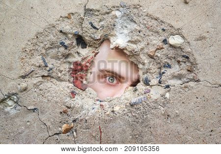 male eye looks through a hole in the concrete wall looking for information spy