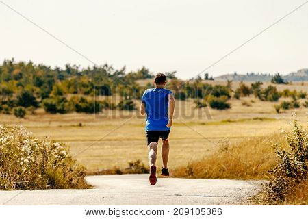 back male runner athlete running on road among field of yellow grass