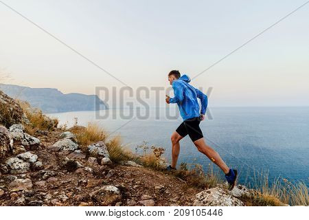 running uphill in trail male athlete runner on sea background