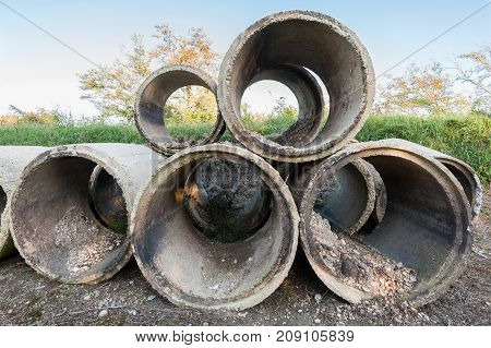 Old concrete tubes. Pipes for drainage. Hoses for construction industry.
