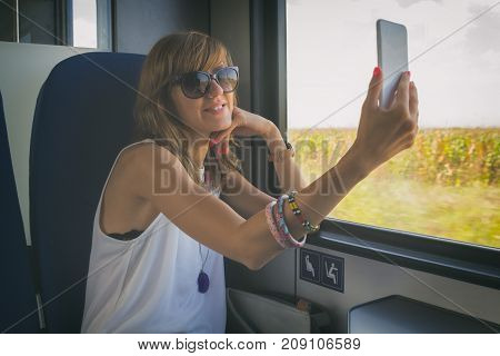 Cute smiley girl using cellphone in the train.