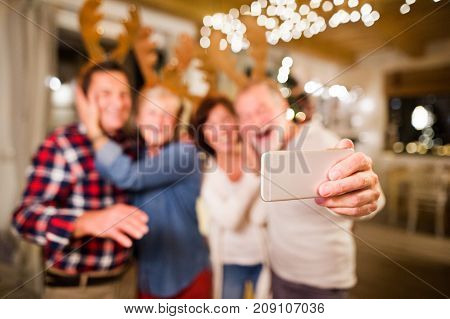 Senior friends wearing reindeer antlers headbands at Christmas time, having fun. Two men and two women with smartphone taking selfie.