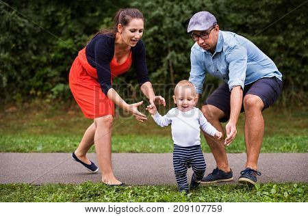 Cute little boy making first steps in nature. Young family spending time in nature. Summer time.