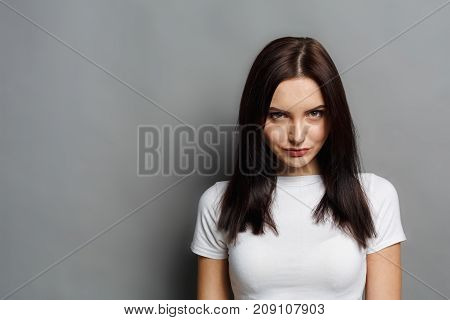 Young brunette woman looking mysteriously at camera on gray studio background
