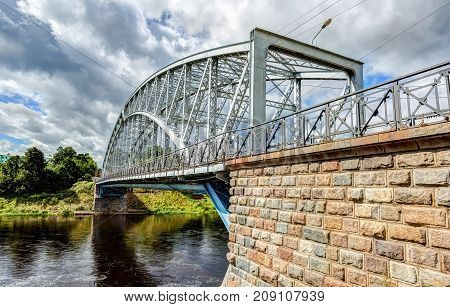 First in Russia steel arch bridge on river Msta in sunny summer day. Was built in 1905. Borovichi Russia