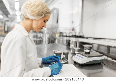 food production, industry and people concept - woman weighing ice cream on scale and filling papers at factory