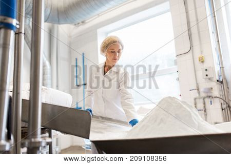 manufacture, industry, food production and people concept - woman working at ice cream factory conveyor with powdered milk